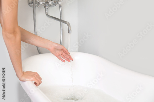 Woman running a bath with warm water and bubbles, closeup Wallpaper Mural