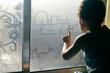 Hand draws on cold fogged window background, closeup image