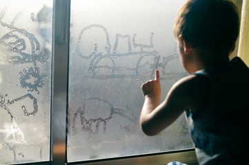 Hand draws on cold fogged window background, closeup image