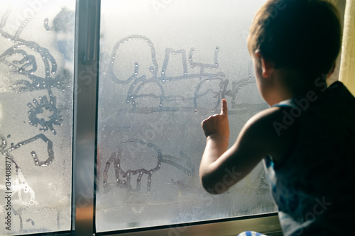 plakat Hand draws on cold fogged window background, closeup image