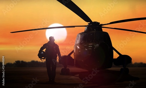 Helicopter silhouette on the ground during sunset