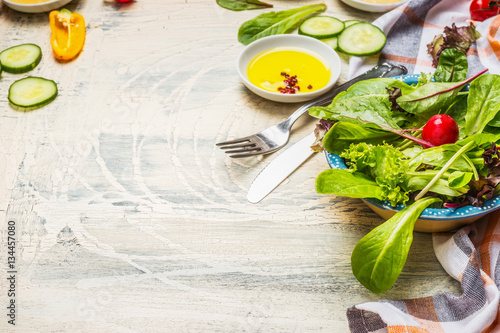 Healthy green salad preparation with dressing and cutlery on