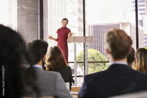 Valokuva  Young woman presenting business seminar gestures to audience