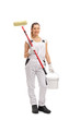 Happy female painter holding paint roller and color bucket
