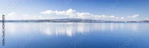 Clear day. Lake Zug in central Switzerland. Clouds are reflected in water lake. At the edge water is clear and see the bottom of the lake.