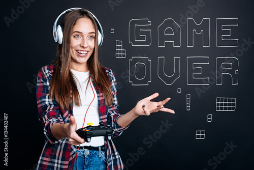 Delighted yong smiling woman playing video games Poster