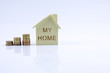 Wooden house model with pile of coin and calculator. House finance concept.
