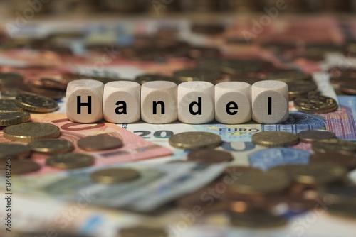 Fotografie, Obraz  handel - Holzwürfel mit Buchstaben im Hintergrund mit Geld, Geldscheine