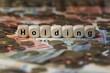 canvas print picture - holding - Holzwürfel mit Buchstaben im Hintergrund mit Geld, Geldscheine