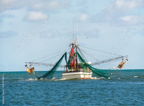 Shrimp trawler fishing boat with nets out on Gulf of Mexico waters by Florida