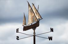 Metallic Ship Weather Vane On Sky Background.
