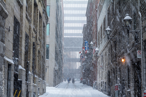 Photo Stands New York Street of Old-Montreal in winter under a snow storm with a modern skyscraper in the background