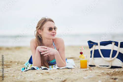 Fototapeta Woman relaxing and sunbathing on beach obraz na płótnie