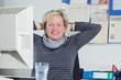 Zufriedene Geschäftsfrau am Schreibtisch im Büro