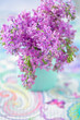 Bouquet of lilacs flowers in a vase on the table.