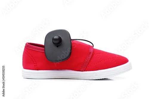 Photo RFID hard tag attached on a red shoe isolated - Shoplifting and anti-theft syste