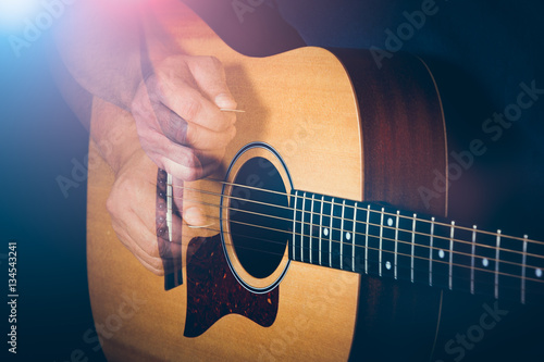 Valokuva  Musician's hand is strumming a yellow acoustic guitar