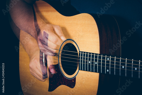 Fotografia, Obraz  Musician's hand is strumming a yellow acoustic guitar