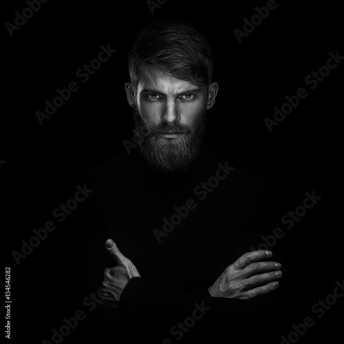 Foto  Portrait of serious young man with arms folded standing isolated