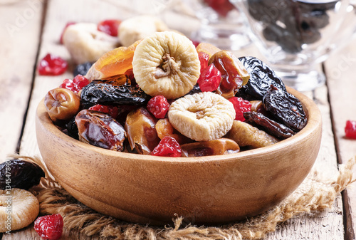 Healthy food: mix from dried fruits in bowl, old wooden backgrou