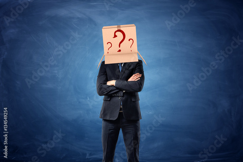 Fotografía  Businessman is wearing cardboard box with drawn question marks on his head