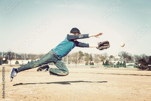 Boy jumpingto catch a baseball