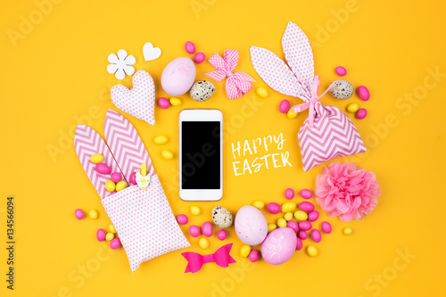 Spoed Foto op Canvas Verenigde Staten Smartphone mock up with Easter decoration: eggs, bunny bag and candy on yellow background