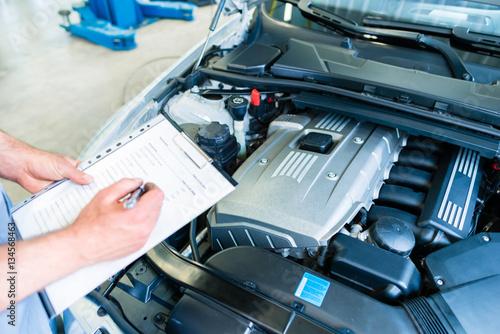 Zdjęcie XXL Mechanik sprawdza samochód z listą kontrolną w auto remontowym sklepie