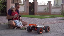 Young Caucasian Kid With His Father Playing With Big Radio Controlled Car Outside In Slowmotion