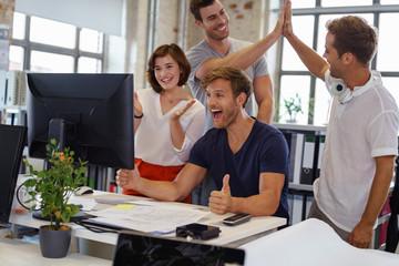 begeisterte kollegen im büro feiern ihren erfolg