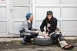 Zwei Frauen mit viel Spaß beim Reifenwechsel