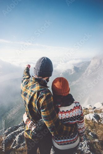 Couple Man and Woman hugging enjoying mountains and clouds landscape on background Love and Travel happy emotions Lifestyle concept. Young family traveling active adventure vacations