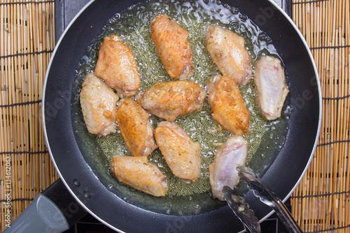 Fotografía  Chef frying chicken wings in pan