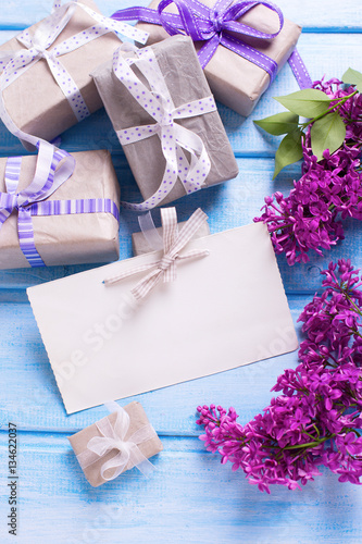 Gift boxes with presents, empty tag and lilac flowers on blue w