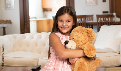 Fototapeta Smiling little girl holding a teddy bear obraz na płótnie