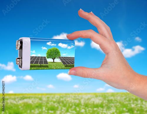 Zdjęcie XXL Ręka trzyma baterię z panel słoneczny. Pojęcie zrównoważonych zasobów.