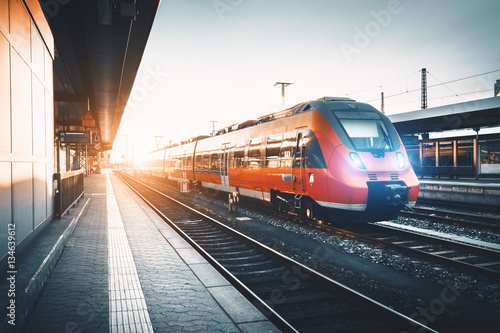 Modern high speed red commuter train at the railway station at sunset плакат