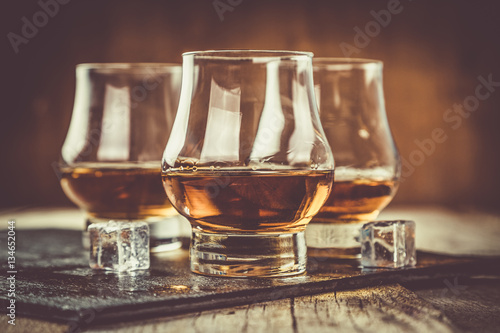 Foto op Canvas Alcohol Whiskey with ice in glasses