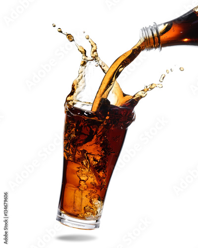 Pouring cola from bottle into glass with splashing Tablou Canvas