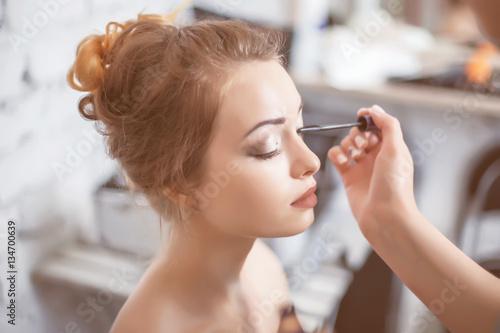Fotografie, Obraz  Make-up artist applying the mascara to model.