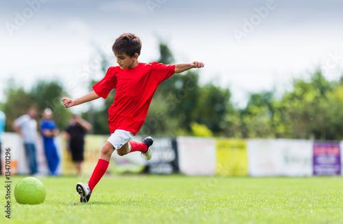 Fotografiet  Boy kicking soccer ball