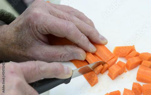 Foto  Seniorenhände schneiden Karotten