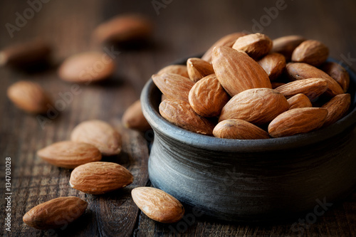 Fotografía Almonds in a black bowl against dark rustic wooden background