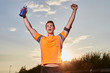 Successful man raising arms after cross country running on summer at sunset