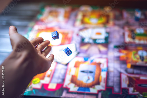 Hand throws the dice on the background of Board games Fototapet