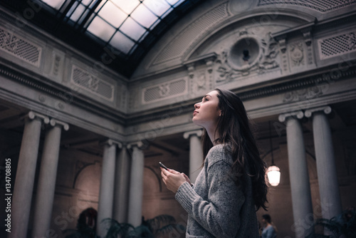 Photographie Portrait of a young attractive woman visiting museum or gallery