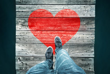 Man Walking And Crossing Aged Narrow Wooden Bridge With Painted Red Heart Symbol, Point Of View Perspective Used. Conceptual Falling In Love Background.