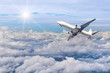 airplane flying away in to sky high altitude above the white clouds with sunlight