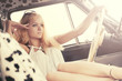 Young fashion blond woman relaxing in vintage car