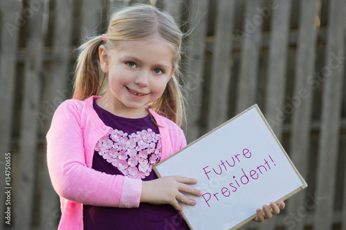 Photo  adorable school age girl wearing pink and holding sign saying future president f